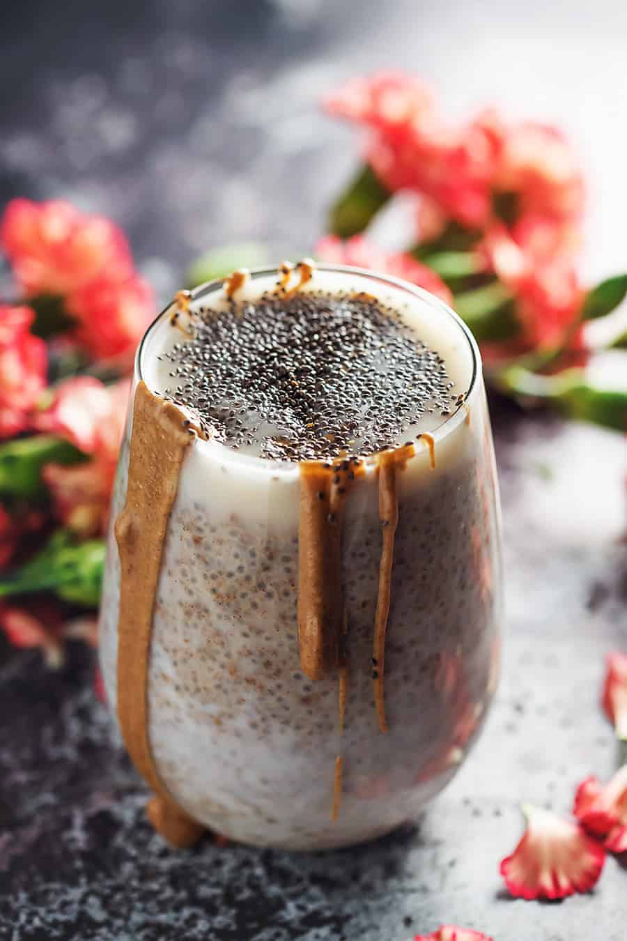 chia seeds pudding in a glass with flowers around