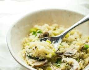 cauliflower risotto in a white bowl with a spoon