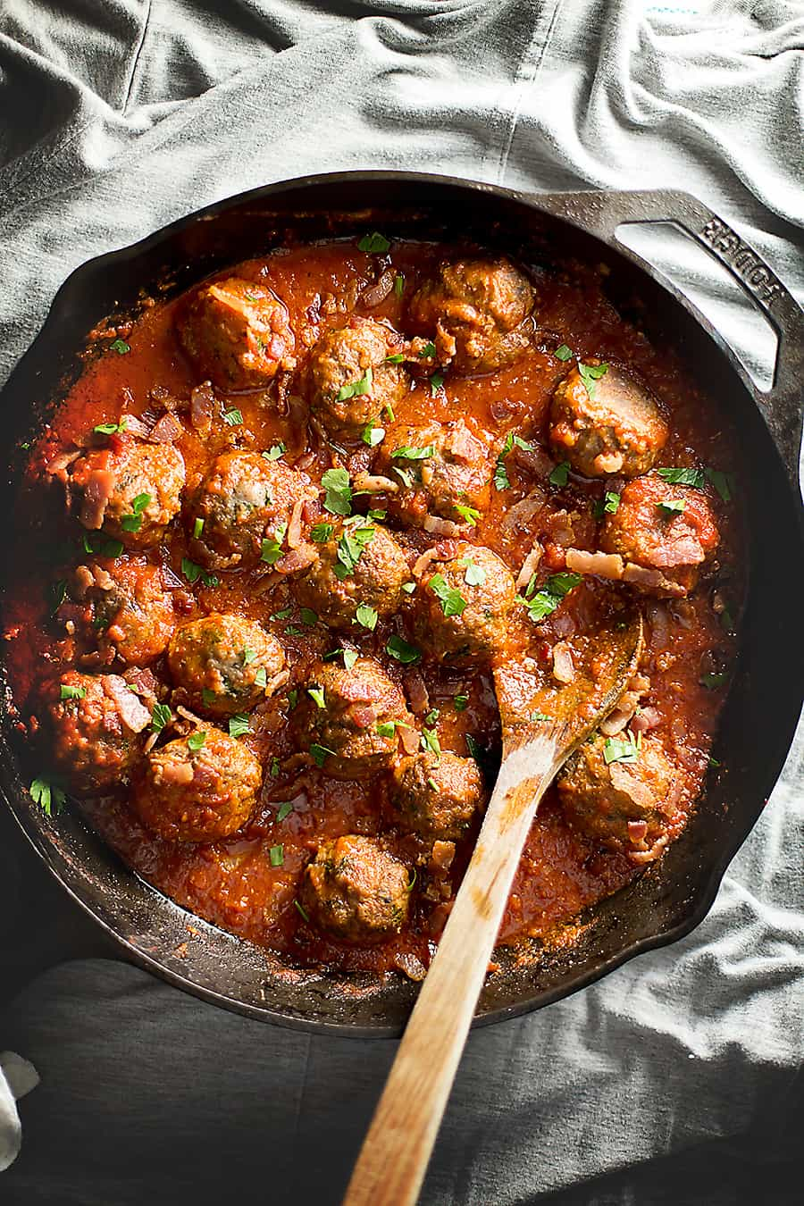 gluten free meatballs with bacon tomato sauce in a cast iron skillet