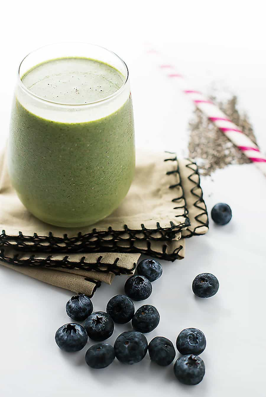 a glass full of a low carb green smoothie on a table with blueberries