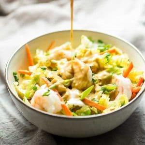 a bowl full of shrimp spring roll bowl salad with peanut dressing being poured over top