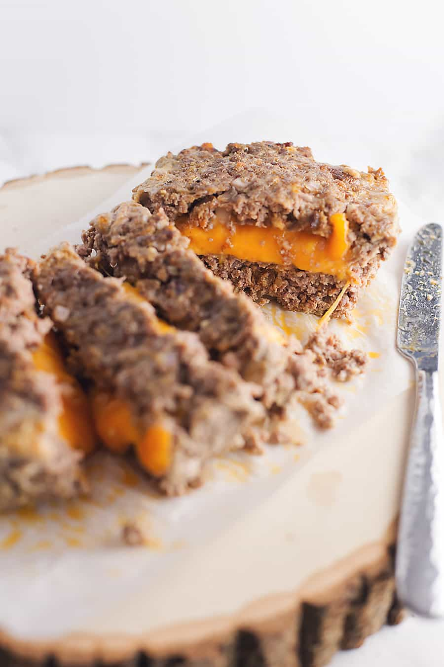 cheese stuffed meatloaf sliced on a wooden cutting board