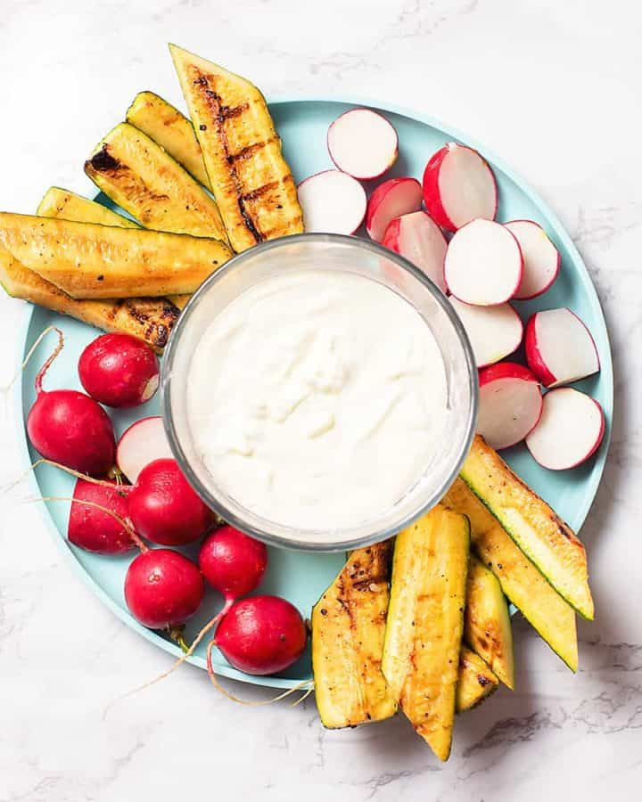 creamy feta vegetable dip recipe in a glass bowl surrounded by roasted zucchini and radishes