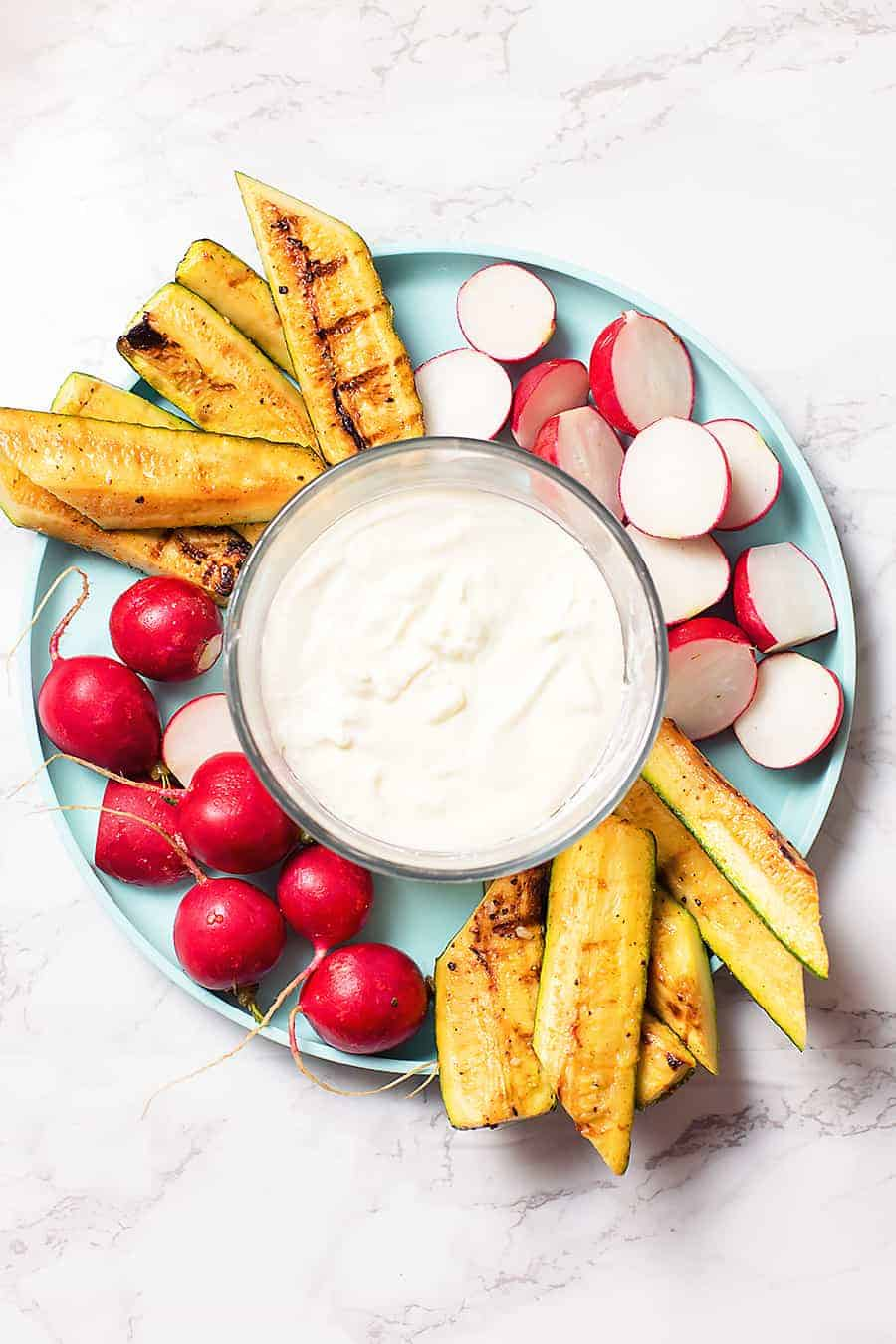 creamy feta dip in a glass bowl surrounded by roasted zucchini and radishes