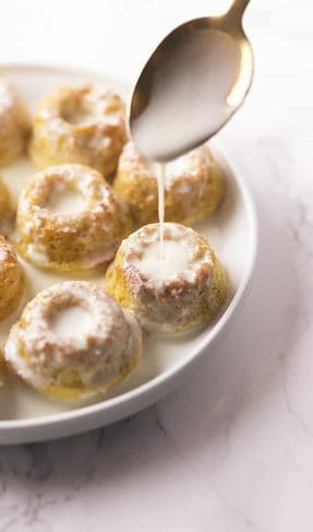 mini donuts soaked in cream on a white plate with a gold spoon pouring the cream over top