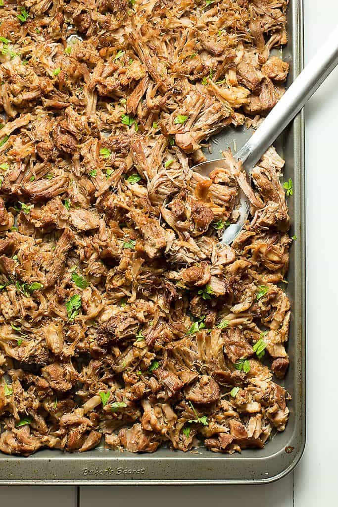 a sheet pan full of pork carnitas with a spoon