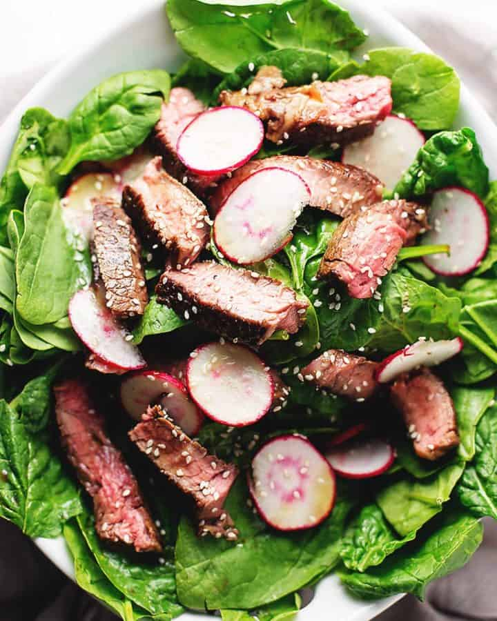 steak salad with radishes and spinach in a serving bowl