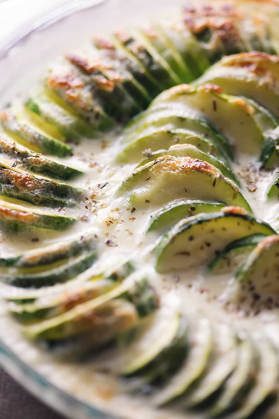 baked cheesy zucchini casserole in a glass pie dish