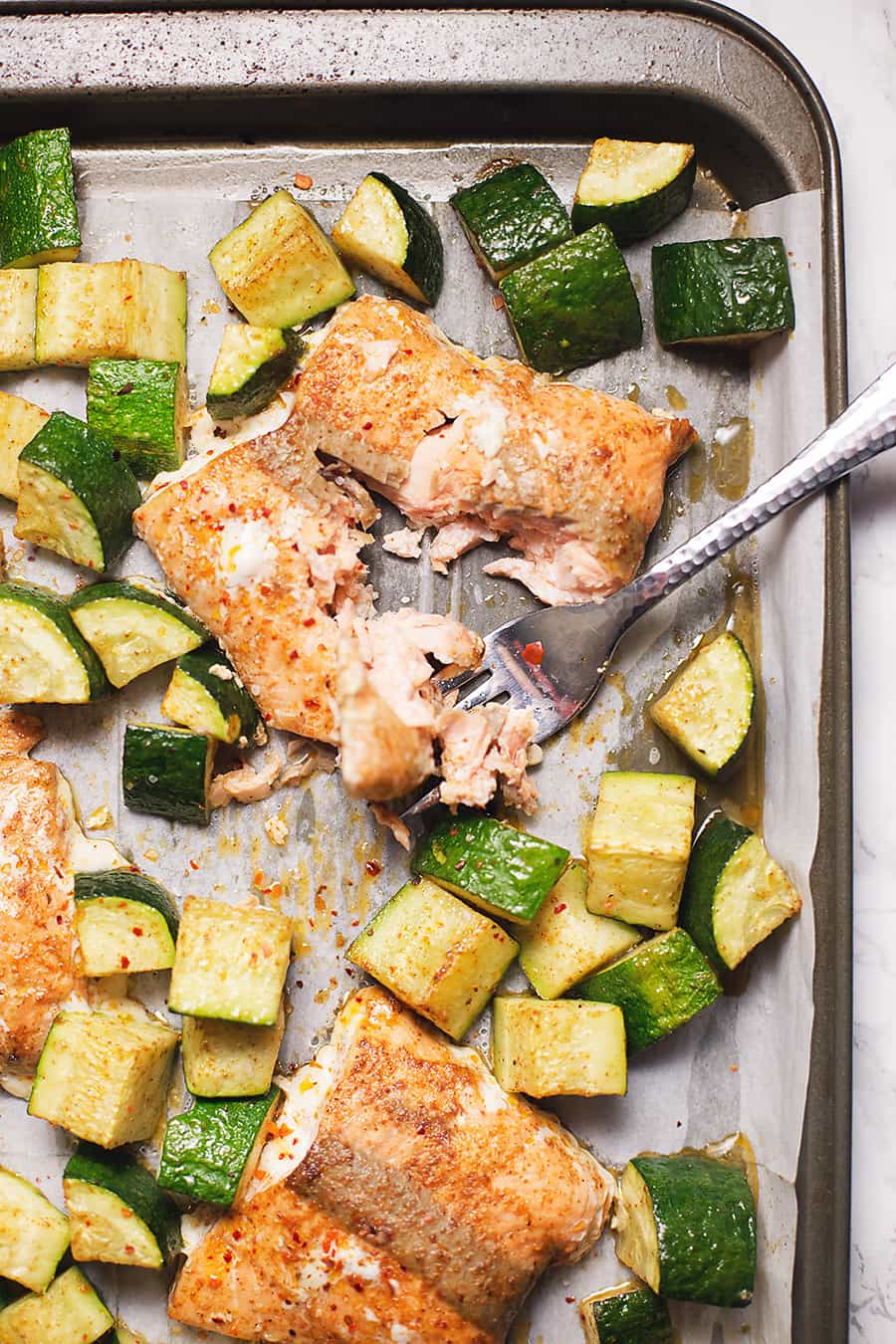 salmon and zucchini baked on a sheet pan