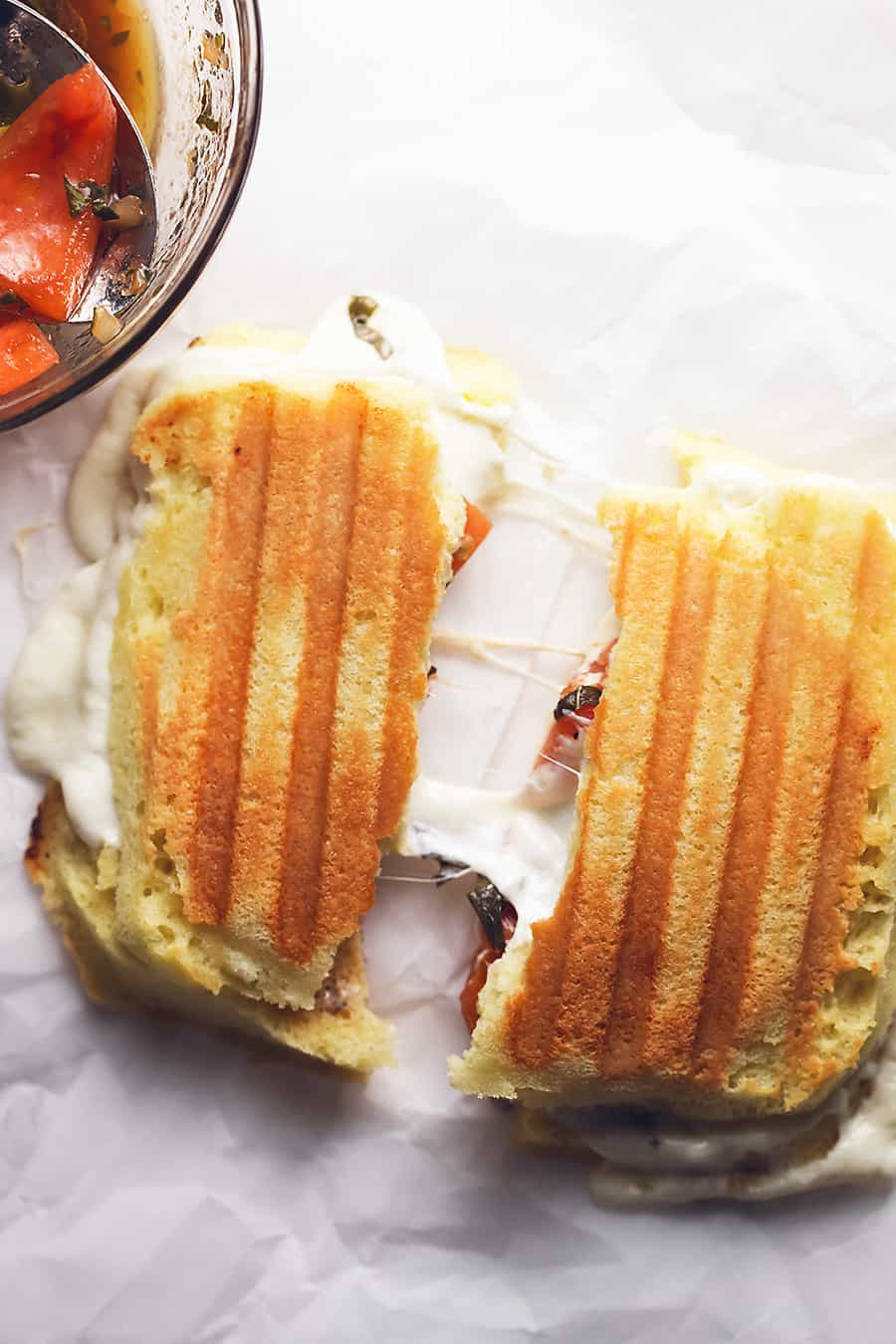 a finished low carb panini with melted mozzarella cheese and tomatoes