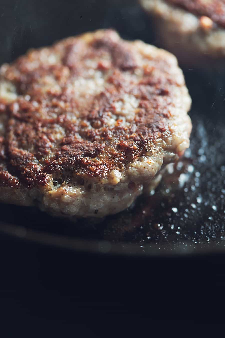 sausage patty cooking in a cast iron skillet