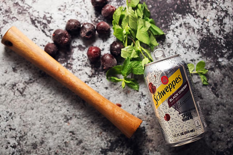 a schweppes black cherry can, mint, frozen cherries, and a muddler