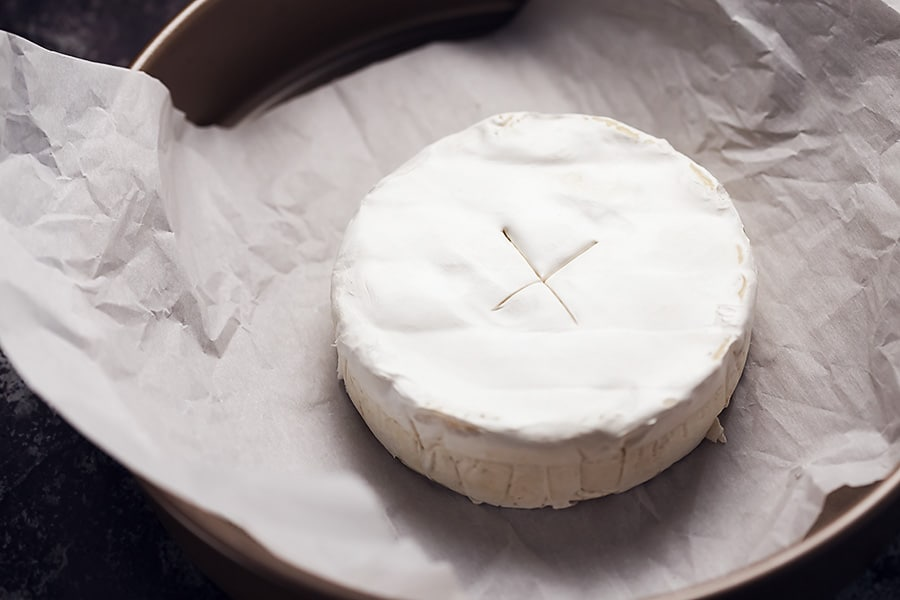 a wheel of brie scored in the middle and sitting on parchment paper