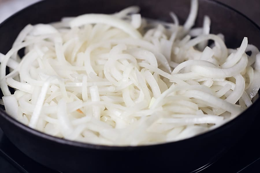 a bunch of sliced onions in a cast iron skillet