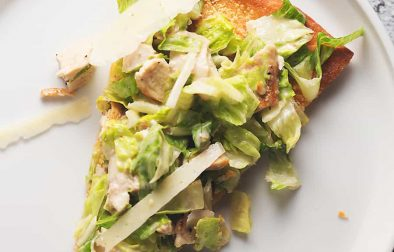 a sliced of chicken caesar salad pizza on a white plate.