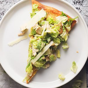 a slice of ceasar salad pizza on a white plate