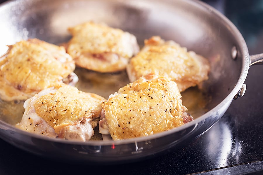 chicken thighs cooking in a skillet