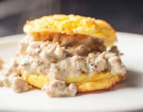 a low carb cheddar biscuit with sausage gray on a white plate