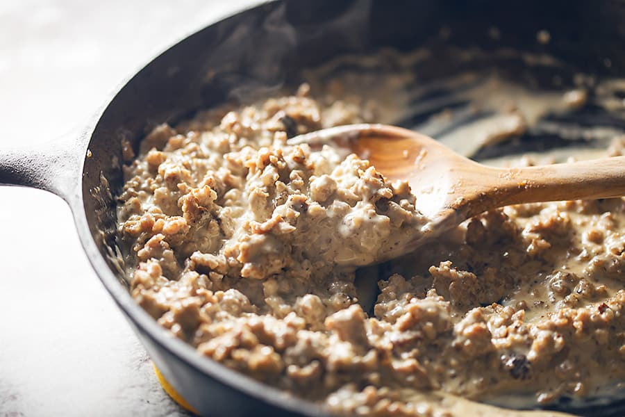thick sausage gravy in a skillet with a wooden spoon