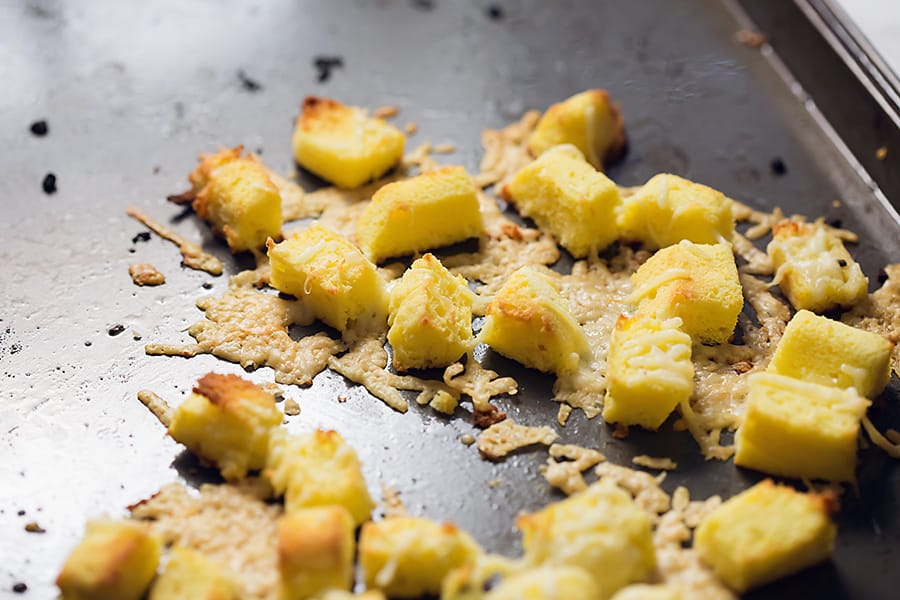 parmesan and croutons on a sheet pan