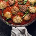 chicken parmesan meatballs in a cast iron skillet with marinara