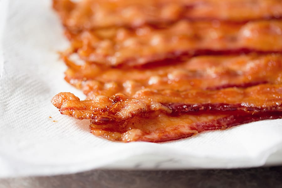 baked bacon draining on paper towels