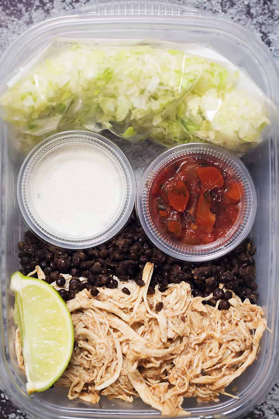 meal prep bowls with lettuce, black lentils, shredded chicken, salsa, and sour cream