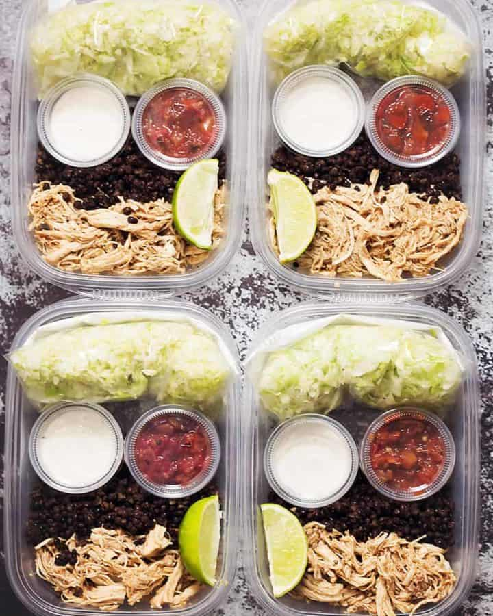 meal prep containers with lettuce, black lentils, chicken breast, sour cream, and salsa