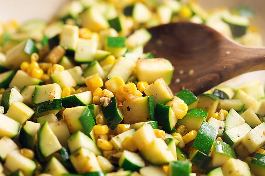 zucchini and corn in a skillet with a wooden spoon