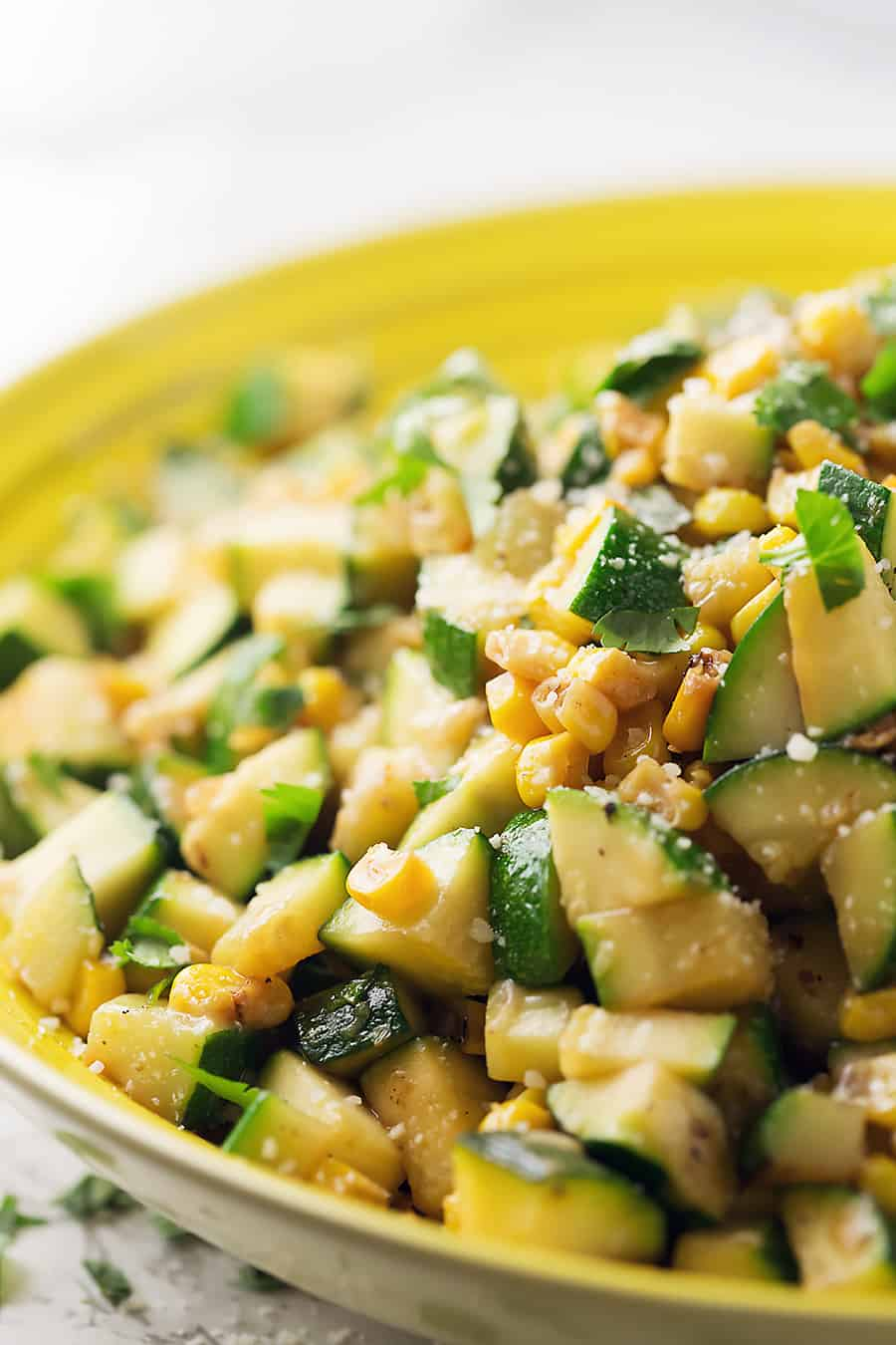 parmesan zucchini and corn diced, cooked and in a yellow serving bowl