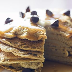 a stack of protein powder pancakes with syrup and chocolate chips
