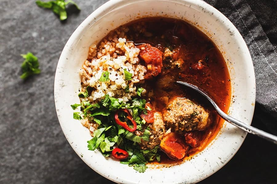 albondigas soup with cilantro and cauliflower rice in a white bowl