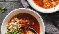 Albondigas mexican meatball soup in a white bowl on a gray background