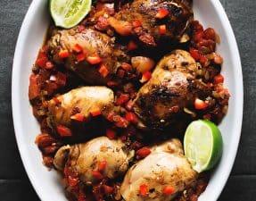 brown stew chicken in a white casserole dish on a dark grey background