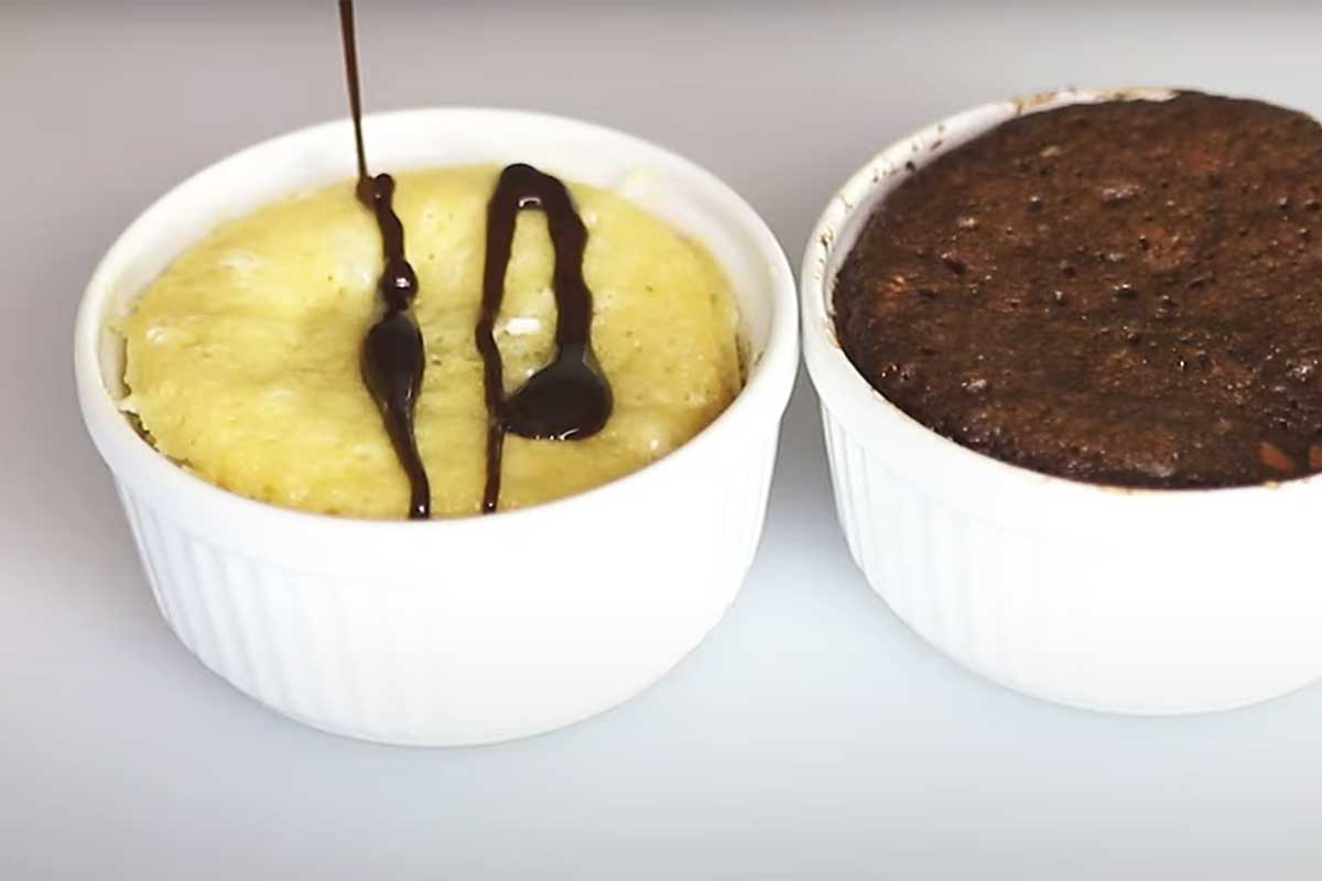 pouring chocolate syrup on a vanilla mug cake