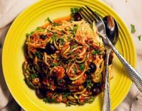 zucchini pasta puttanesca in a bright yellow bowl