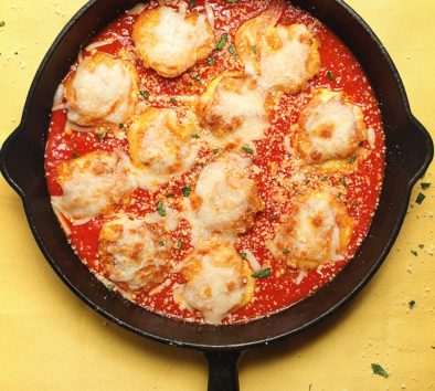shrimp parmesan in a cast iron skillet on a yellow table cloth