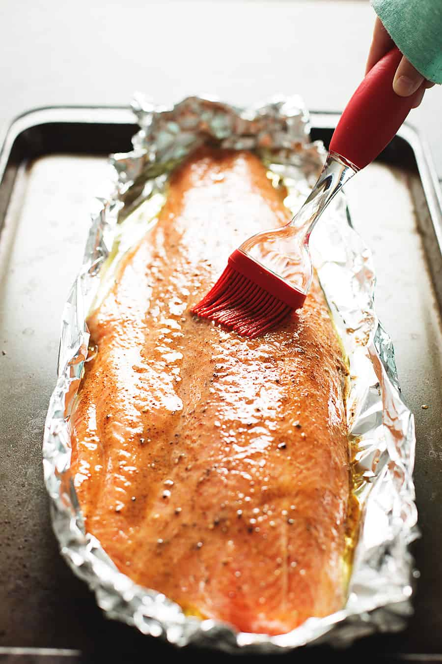 a salmon filet in foil with a basting brush
