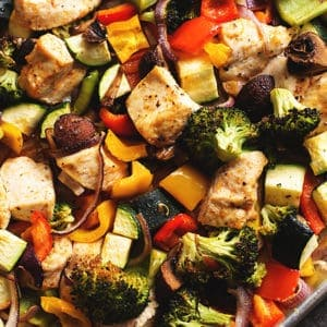 a sheet pan with cooked chicken and veggies