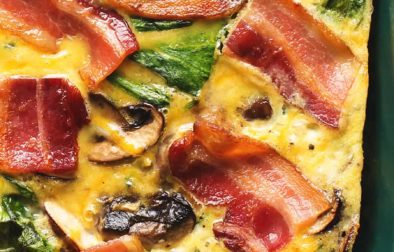 breakfast casserole with strips of bacon on top in a dark green dish