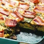 Low carb breakfast casserole in a green dish with a piece of casserole missing