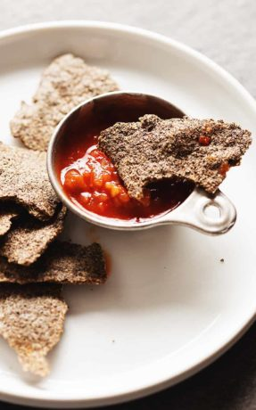 low carb tortilla chips on a white plate with salsa