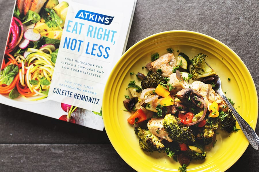 Atkins eat right not less book and a yellow bowl full of chicken and veggies