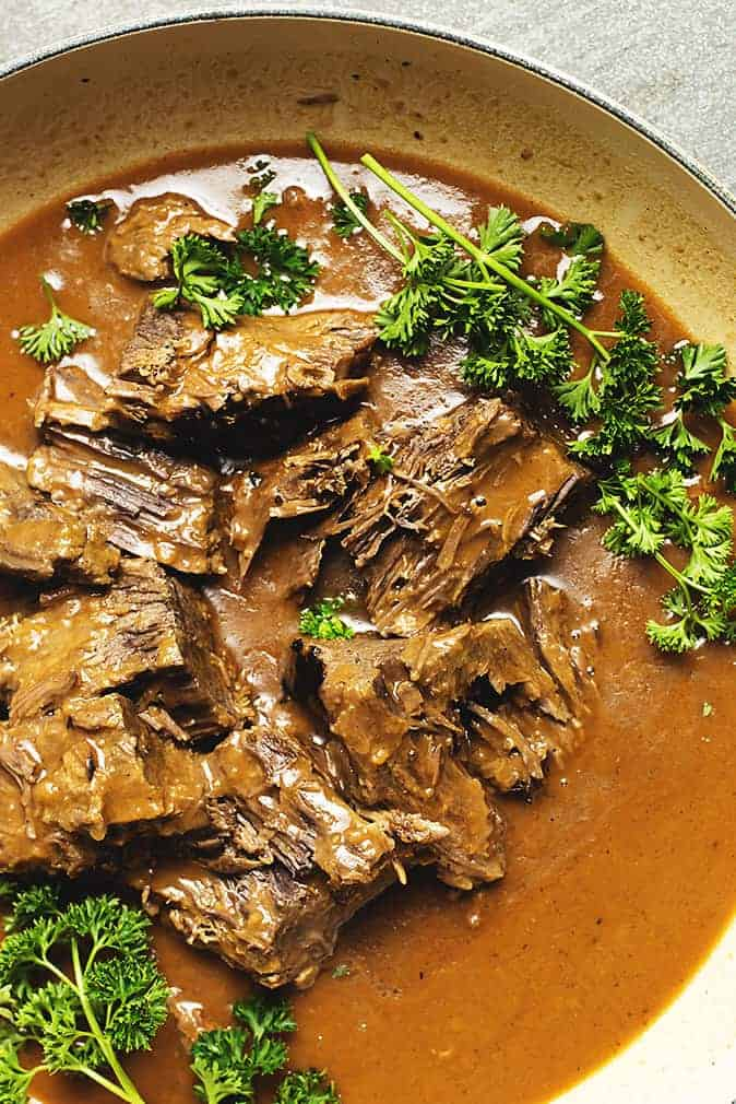 rump roast and gravy with parsley in a skillet