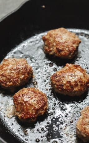 turkey sausage patties cooking in a skillet