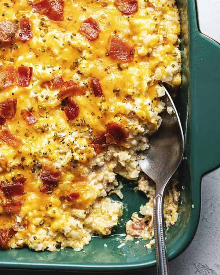 cheesy loaded cauliflower rice casserole in a green dish