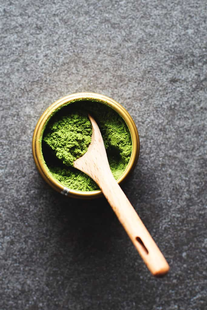 matcha green tea powder with a wooden spoon