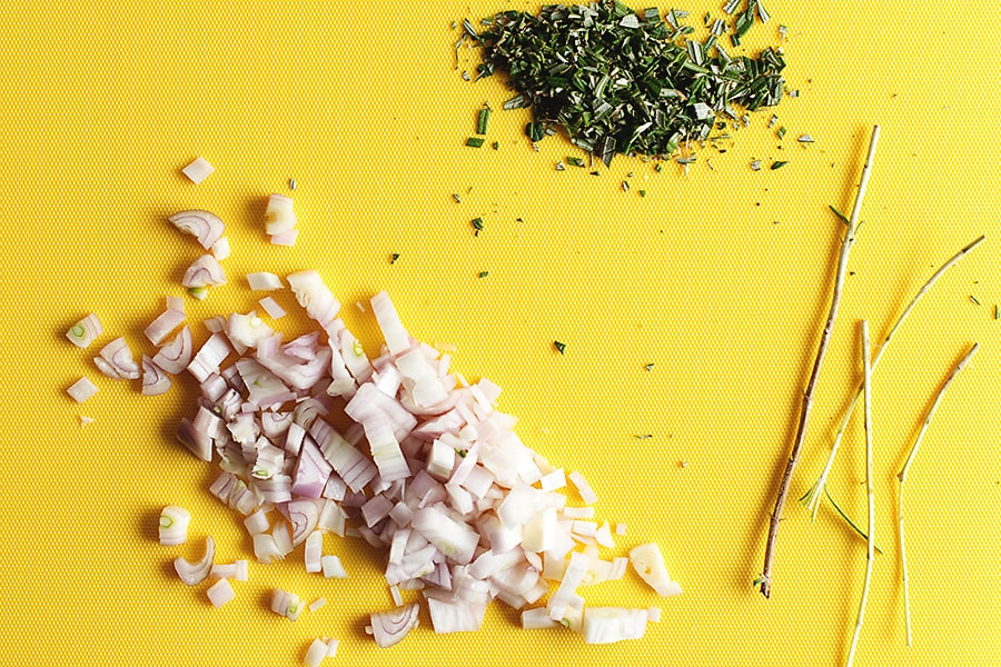 diced shallot and rosemary on a yellow cutting board