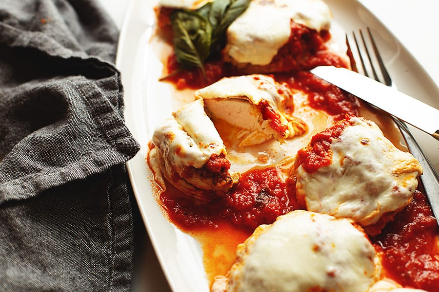 Chicken parmesan cut on a white plate