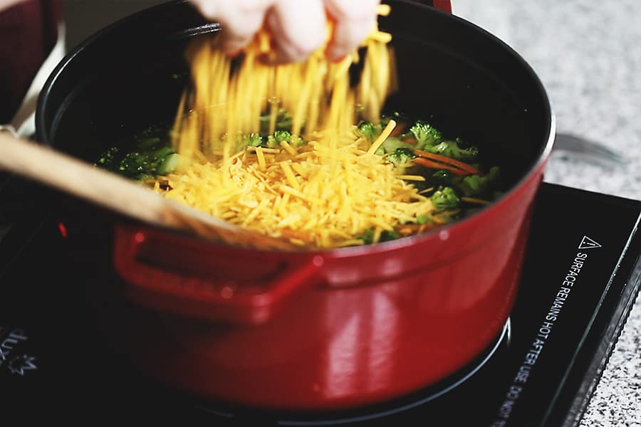 adding cheddar cheese to the red pot full of broccoli